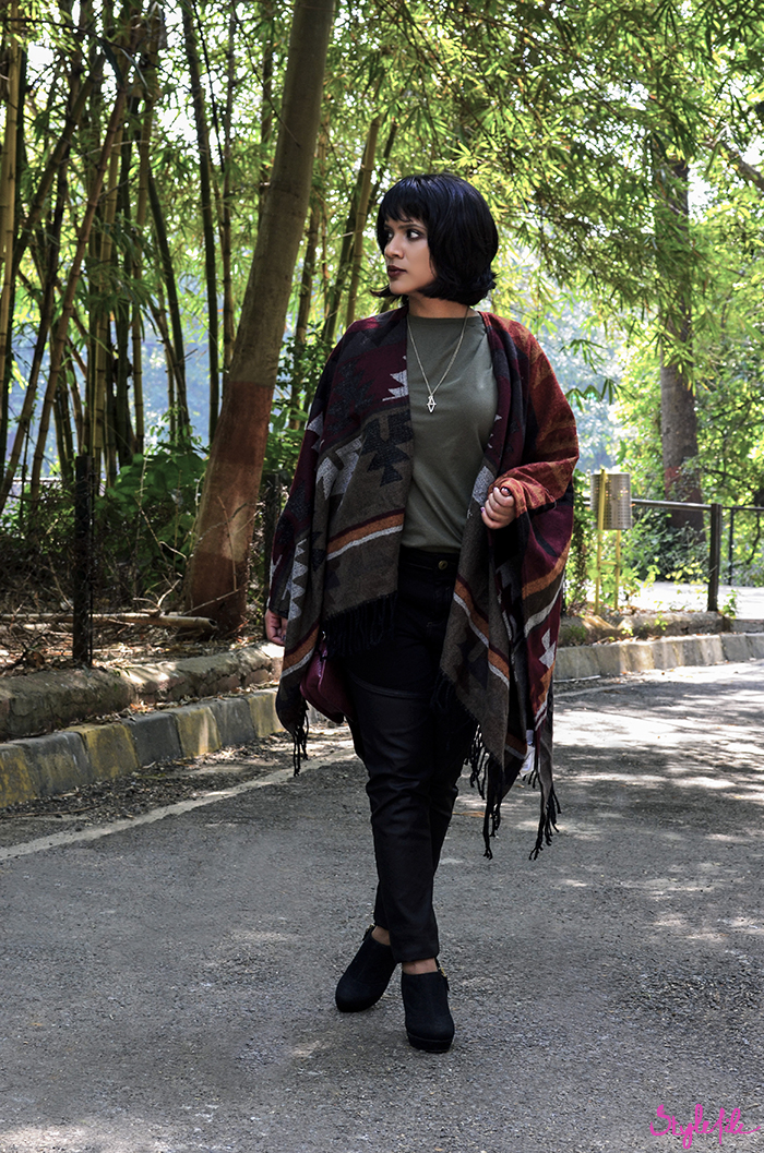 Image of a girl wearing an autumn winter outfit of a navajo print poncho coat, leather panel black jeans, black booties, plum copper eye makeup and a dark brown lip