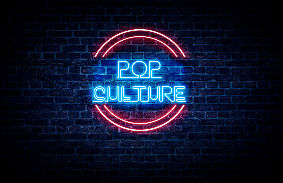 A pink and blue neon sign that's flashing Pop Culture.