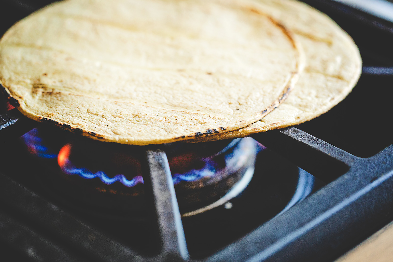 Corn tortillas warmed on a gas stove.