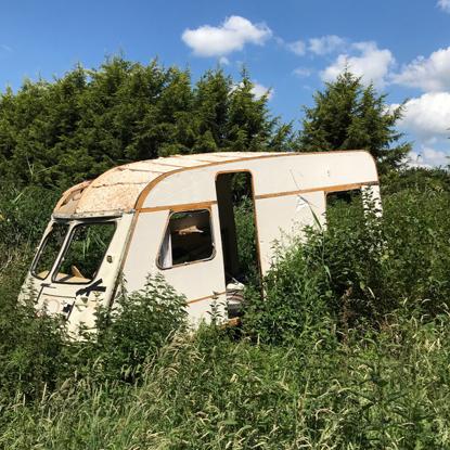 a derelict caravan in an overgrown field