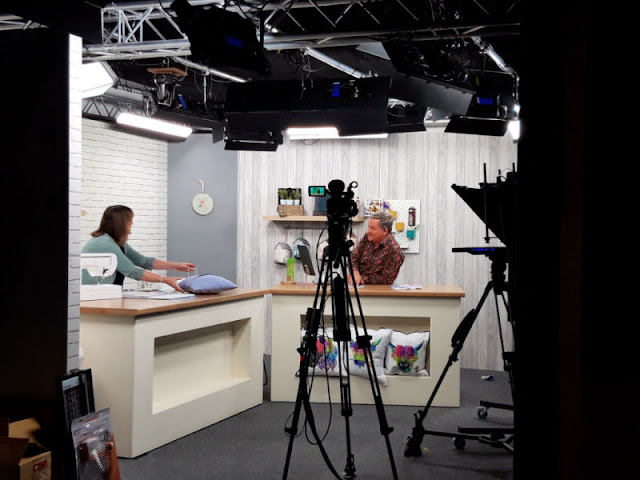 A behind the scenes photo of the TV studio.  A lady is showing the presenter a cushion.  Two large tables are set at an angle to each other and there are cameras facing them
