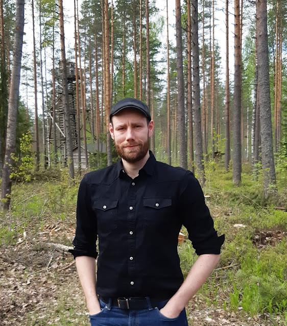 Jani Loijaksen henkilökuva ulkona. Taustalla näkyy vartiotorni.