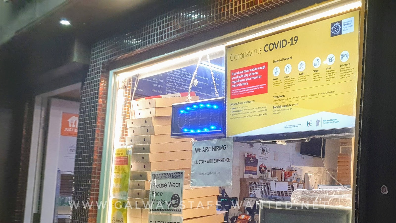 Pizza shop window, with television screen Covid warning sign taking 1/4th of the space, and a pile of pizza boxes in the corner