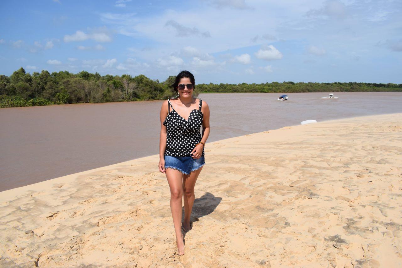 mulher em frente a um rio com arvores submersas