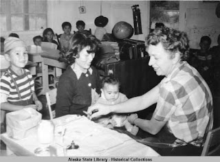 A nurse preparing a vaccine for a baby sitting on a woman's lap. A young boy stands behind the woman's chair.