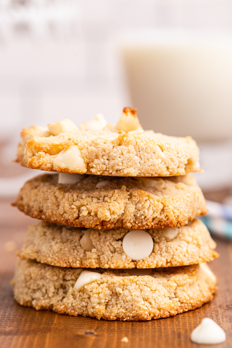 Close up photo of a stack of Keto White Chocolate Macadamia Nut Cookies on a wooden table with a glass of milk in the background.