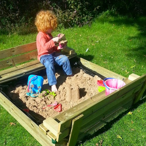 4 year old sitting playing in sand pit on lawn hinged lid forms seats
