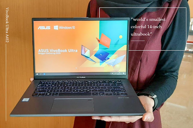 seorang model memegang laptop asus ditangannya