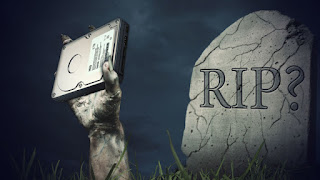 A gravestone labeled RIP?, with an arm coming from it holding a drive.