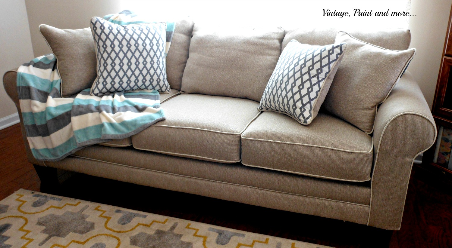 a neutral sofa with colorful coastal accessories