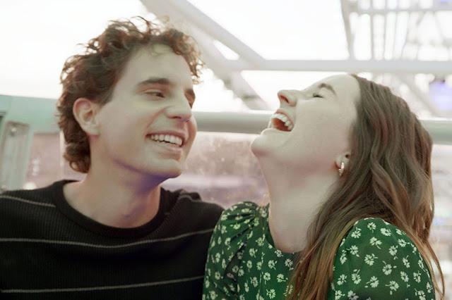 A boy and girl laugh at an amusement park