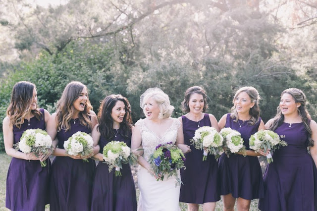 bridesmaids in short plum dresses and bouquets