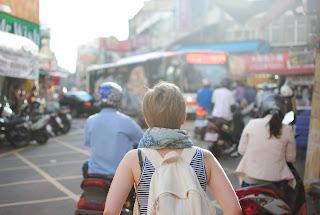 viajera en una calle atestada con motociclistas y autobus