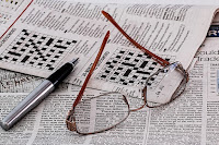 newspaper crossword with eyeglasses resting on the newspaper