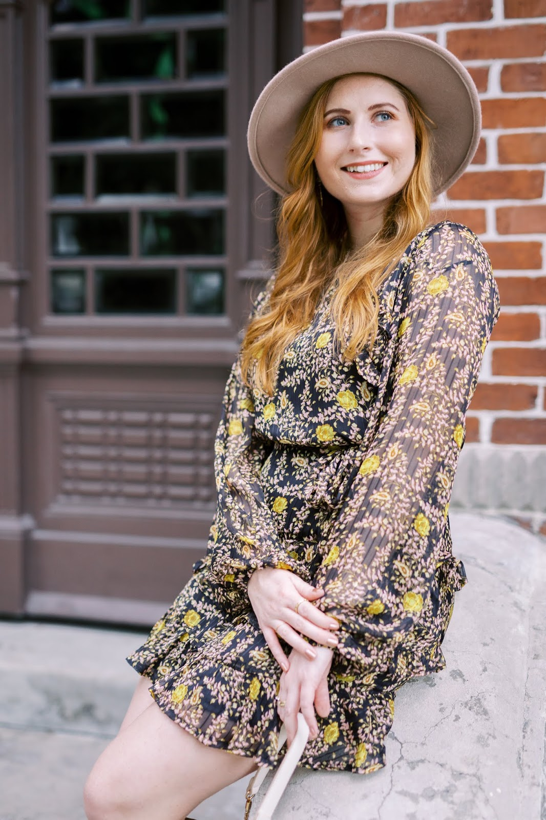 Stylish and Affordable Thanksgiving Outfit Ideas: 20 Dress Options To Wear on Thanksgiving | Amanda Burrows of Affordable by Amanda wearing a black, yellow, and sheer ruffle dress. She is smiling and wearing a Free People felt hat.