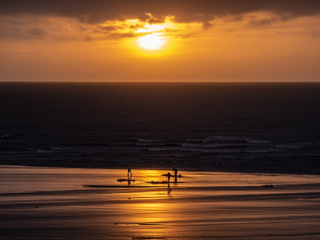 Photo of fishermen digging bait on Maryport beach at sunset
