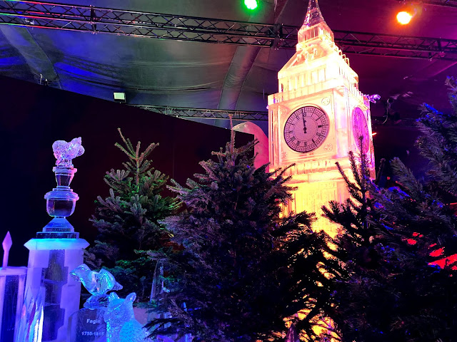 an ice carving of big ben behind some Christmas trees