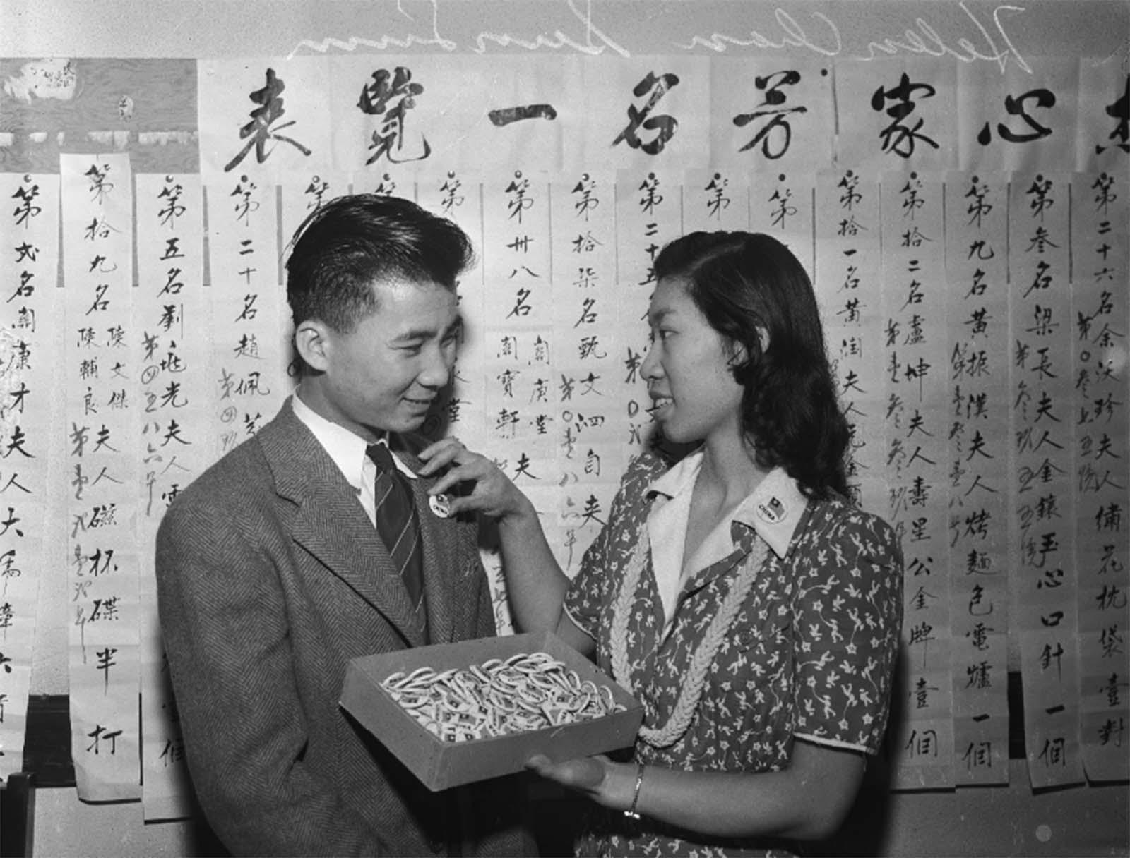 Helen Chan coloca Sun Lum com um distintivo de lapela identificando-o como