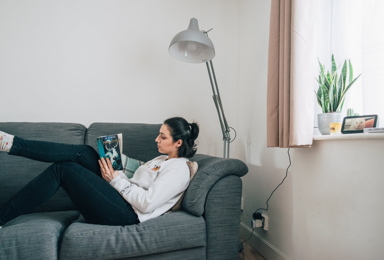 A girl lounging on a grey sofa reading a book with her legs crossed at the knee.