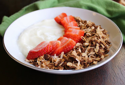bowl of yogurt with slices of strawberries and chocolate granola