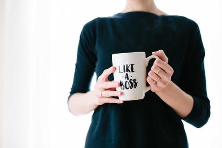 """woman holding mug which states """"like a boss"""""""