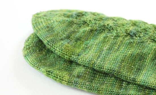Detail of hand-knit green socks with darned toes and ball of the foot on a white background.