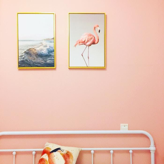 Cuadros con marcos dorados sobre pared rosa