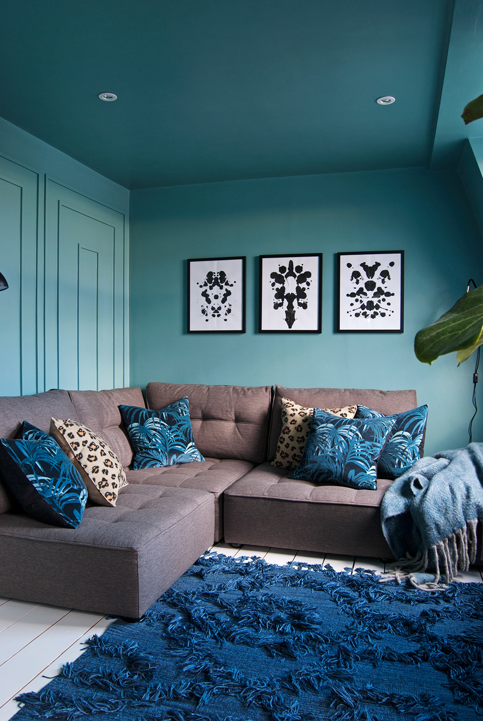 Family TV Room Reveal - French For Pineapple Blog - Teal blue room with brown sofa and velvet House of Hackney cushions, shaggy blue rug, and decorative wall moulding.