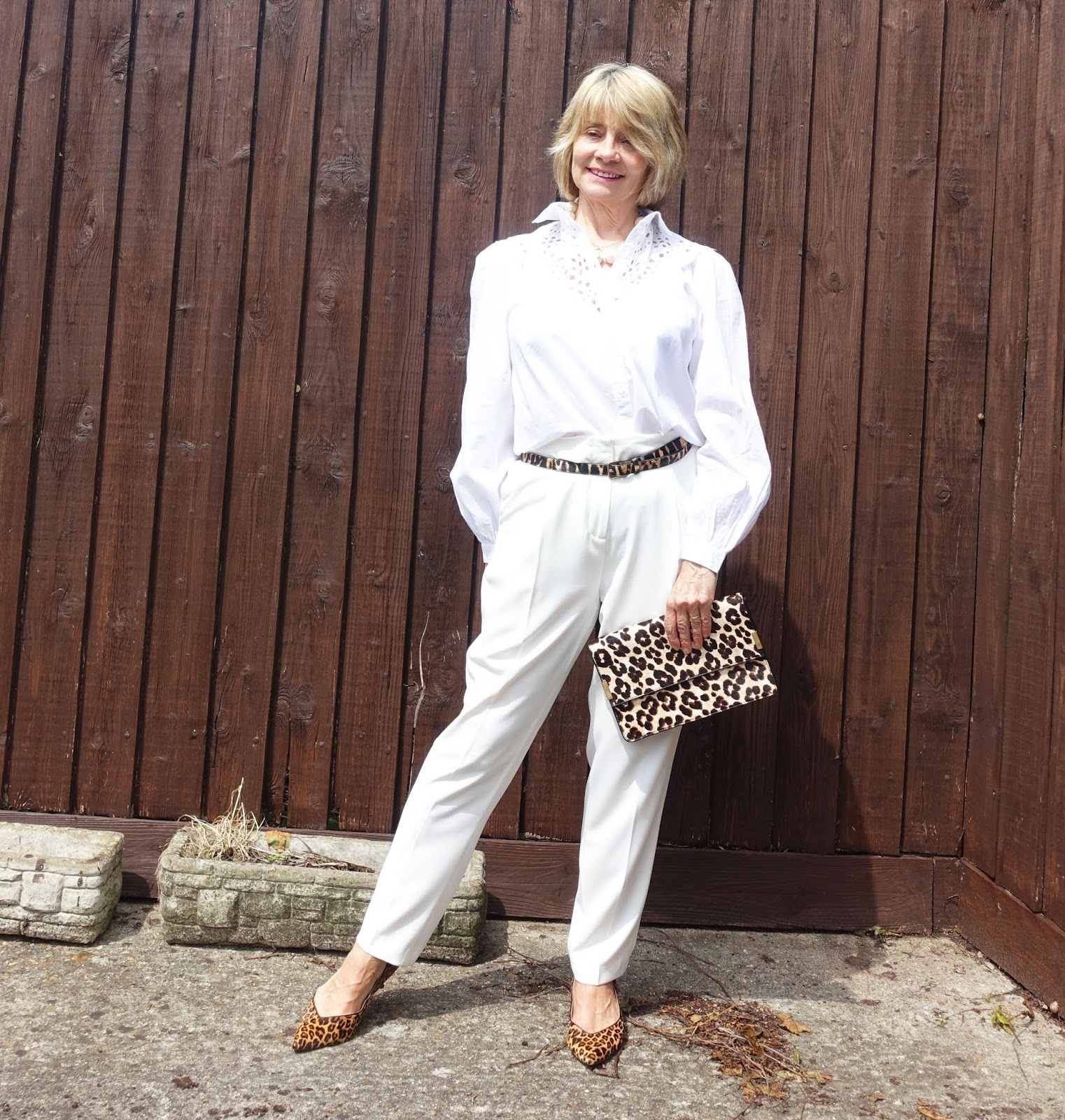 Over 50s fashion blogger Gail Hanlon from Is This Mutton in white trousers, broderie blouse and leopard print accessories