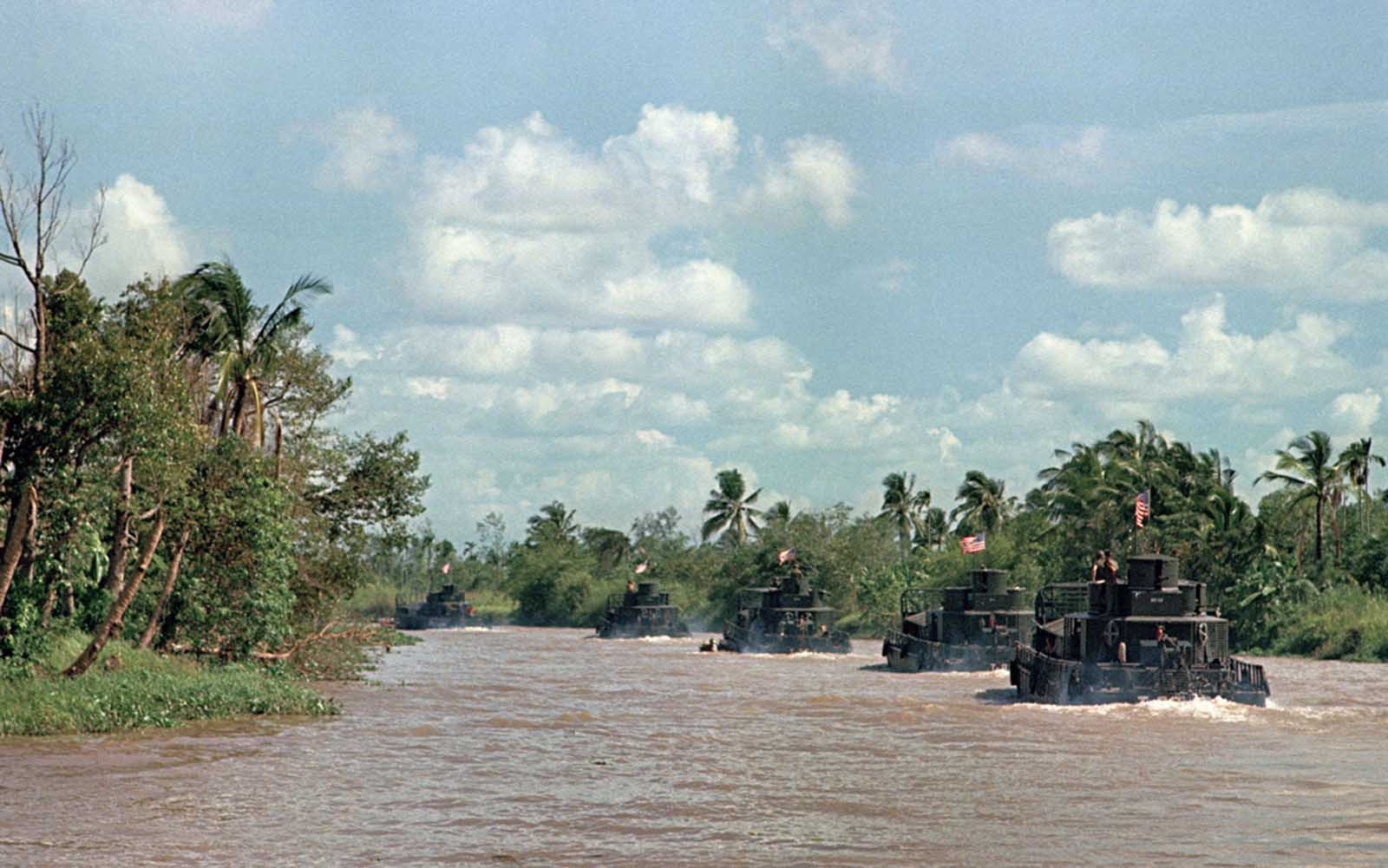 Assault boats in the Mobile Riverine Force of the U.S. 9th Infantry Division glide along the My Tho River, an arm of the Mekong Delta near Dong Tam, 35 miles southwest of Saigon, on March 15, 1968.