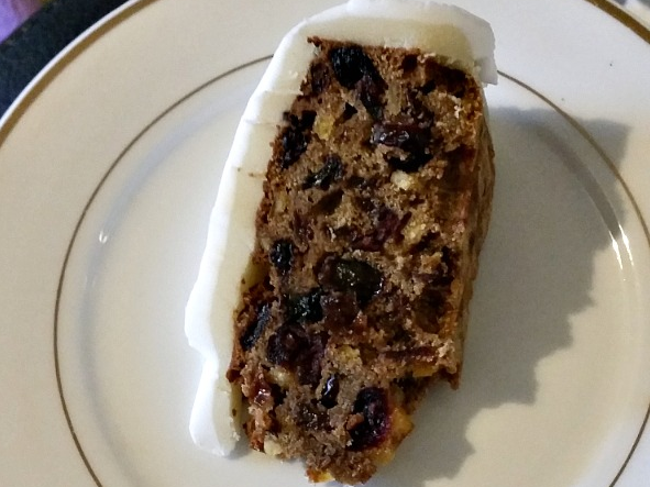 A slice of Christmas cake on a white plate.