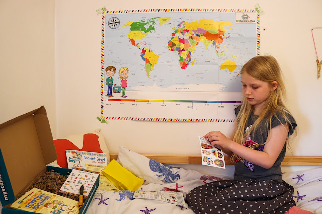 A girl investigating the Mysteries in Time subscription box she received to review