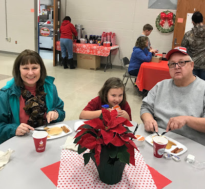 A man, woman, and child sitting at a table enjoying their breakfast