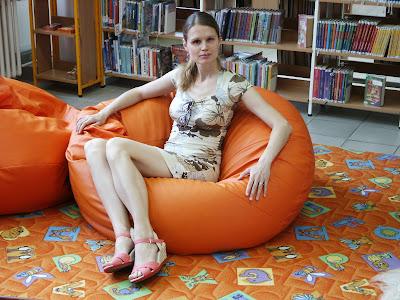 Linda sedí na sedacím vaku v knihovně