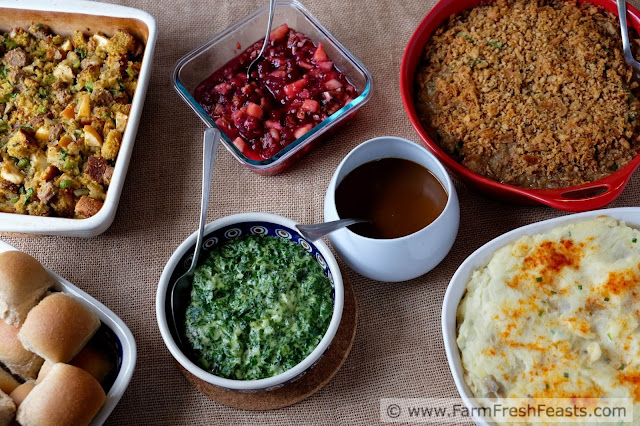 image of a Thanksgiving side dish layout, with stuffing, rolls, creamed spinach, cranberry sauce, green bean casserole and mashed potatoes. Oh, and gravy. I always forget the gravy.