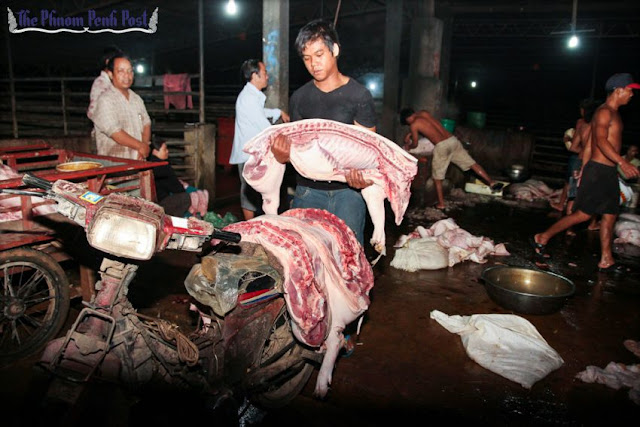 A man loads pork onto a motorcycle at a Russey Keo district slaughterhouse in 2014. Hong Menea