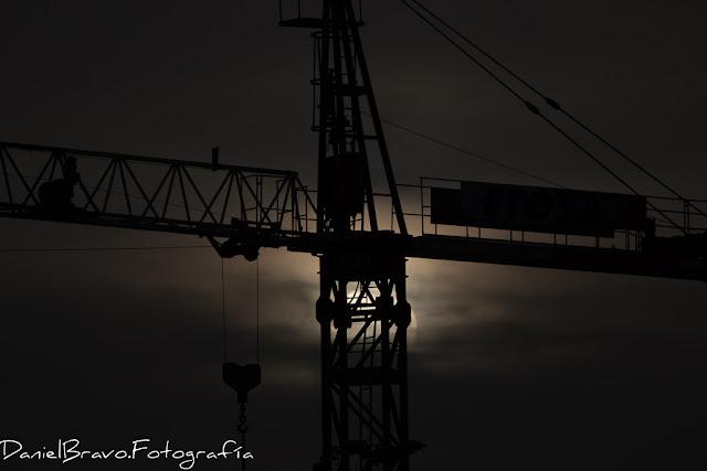 fotografía de una grúa de obra a contraluz con el Sol detrás de ella entre nubes