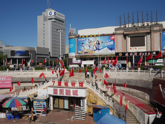 Chinese and red flags surrounding the Guomao Shopping Center (国贸商城) at Culture Square (文化广场) in Mudanjiang, China