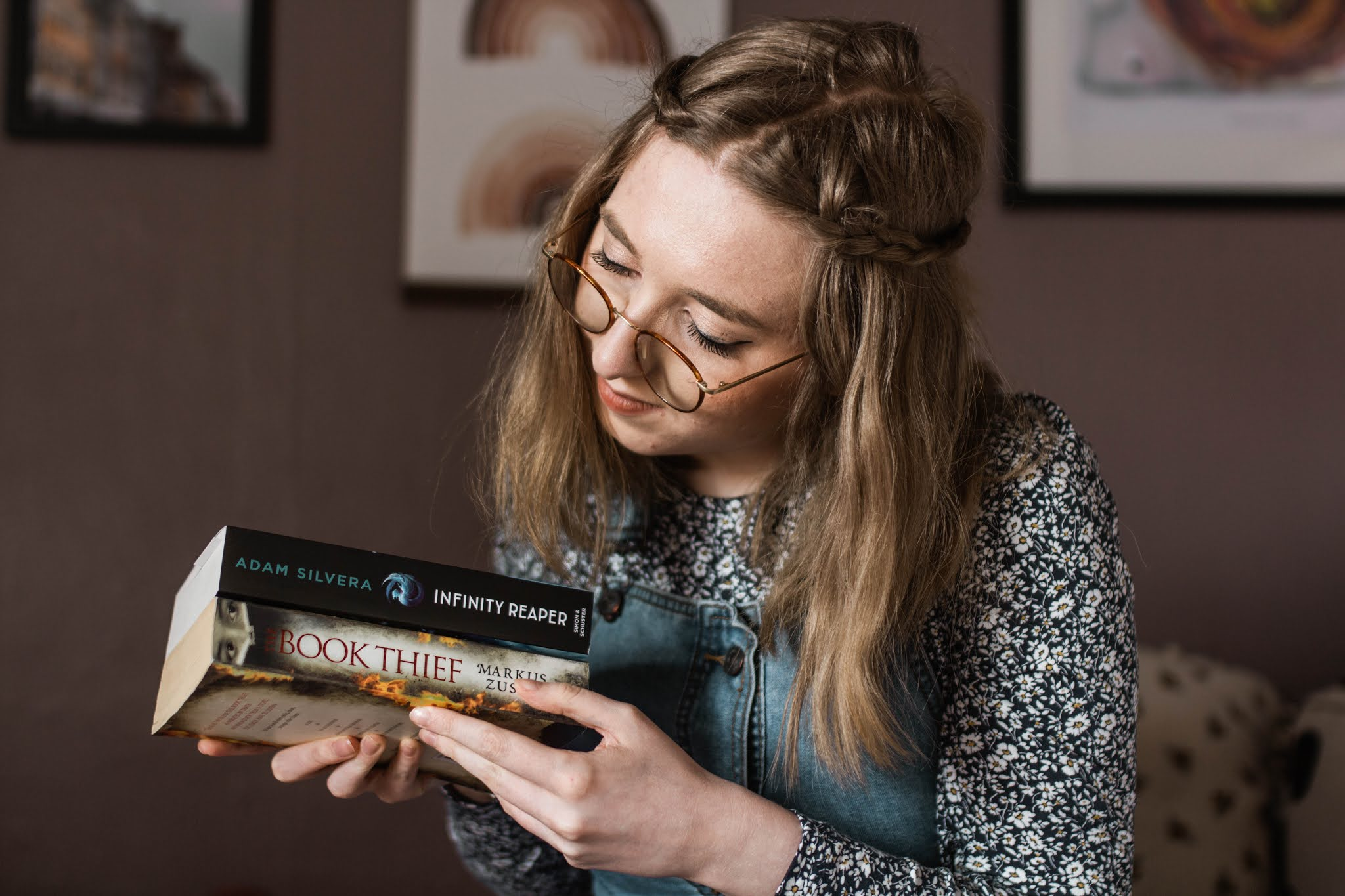 girl in blue holding book stack