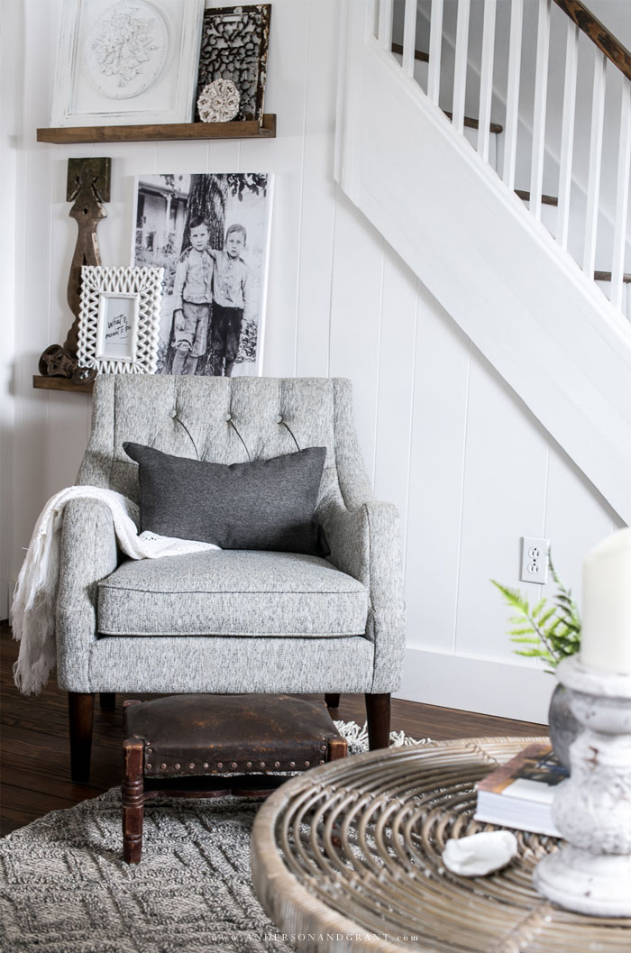 Gray living room chair in front of picture ledge shelves