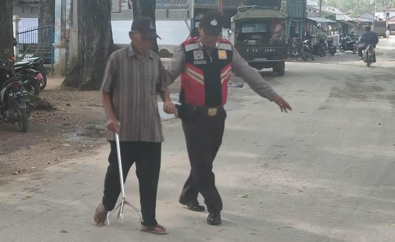 Tanamkan Sifat Perduli, Brigadir Hariono Bantu Kakek Menyeberang Jalan