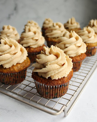 cooling rack full of banana cupcakes with swirls of peanut butter buttercream
