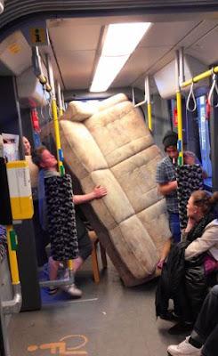 Witzige Frau in Straßenbahn - Couch transportieren