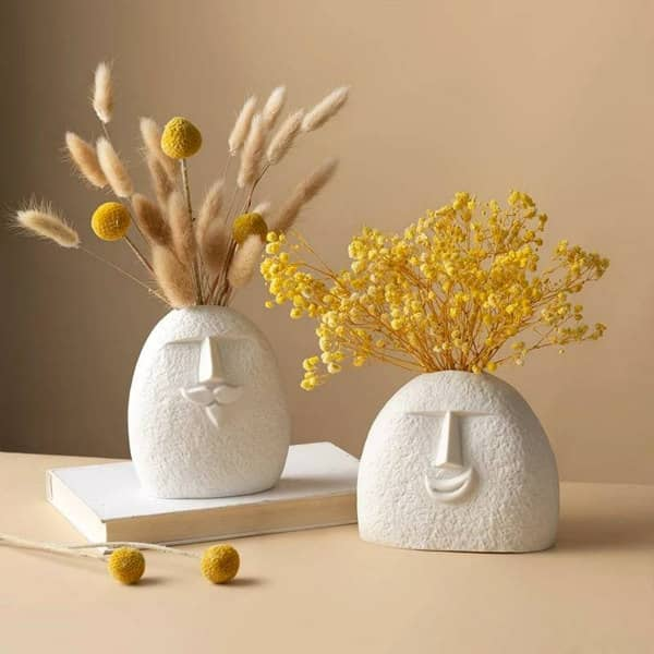 pair of minimalist head vases with soft wildflower arrangements in neutrals and yellow