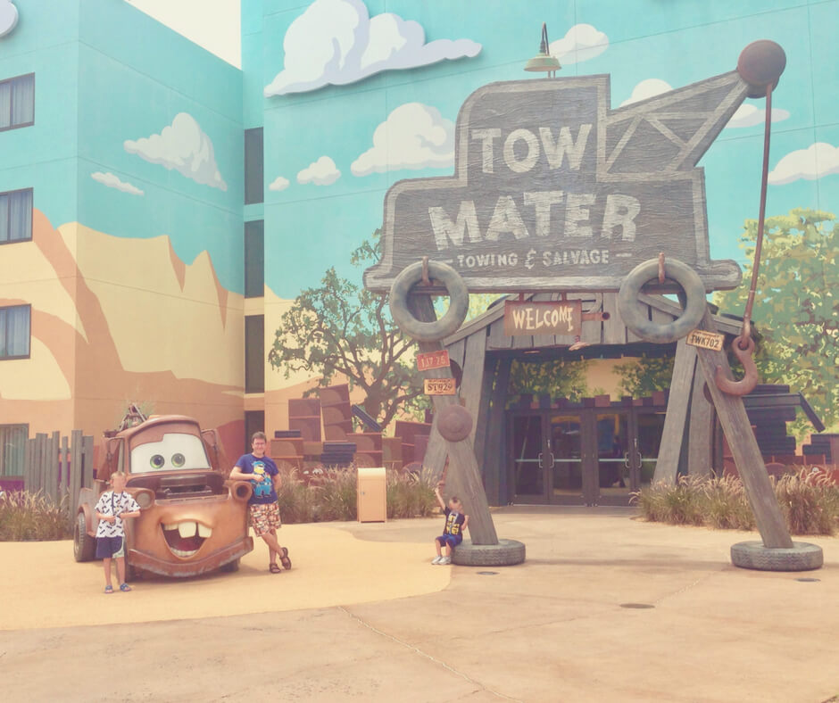 Three boys stand next to Tow Mater from Cars featured at Art of Animation hotel in Walt Disney World.