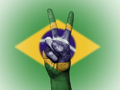 Bandeira do Brasil, projetada sobre mão fazendo gesto de paz e amor. #PraCegoVer