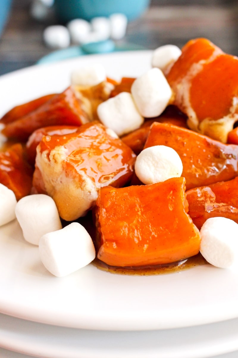 Side view of Candied Sweet Potatoes with Marshmallows on a white plate on a rustic wood background.