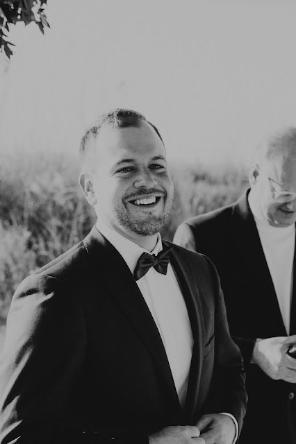 Groom candidly laughing at destination wedding.