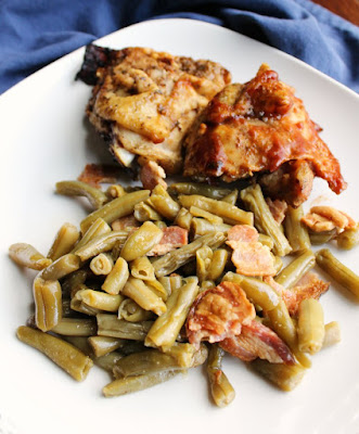 Dinner plate loaded with smothered green beans and bacon and bbq chicken