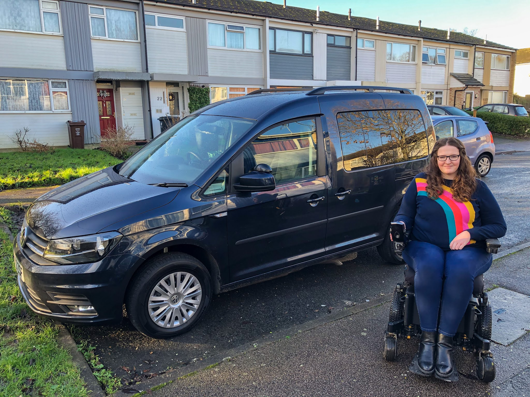 Shona, a young white woman with long curly auburn hair, is sitting in a powerchair in front of a midsize wheelchair accessible vehicle. She is wearing dark blue jeans, black boots and a navy jumper with a rainbow on, she is also wearing glasses. The car is a dark navy colour, it is a VW Caddy.